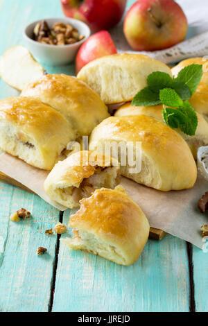 Hausgemachter Apfelkuchen mit frischen Äpfeln und Walnüssen aus Hefeteig auf einem Küchentisch aus Holz. Apfel-Bratlinge - Stockfoto