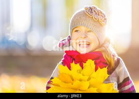 Glückliche kleine Mädchen mit Herbstlaub - Stockfoto