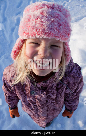 Ein Kleinkind, pelzigen rosa Hut lächelnd in die Kamera. - Stockfoto
