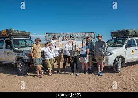 Touristen posieren vor dem Wendekreis des Steinbocks Zeichen in der Namib-Wüste, befindet sich in Namibia, Afrika. - Stockfoto