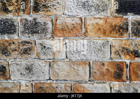 Ein Abschnitt einer Sand Steinmauer zeigt satte Farbe und ein sogar Verlegung des Steins. - Stockfoto