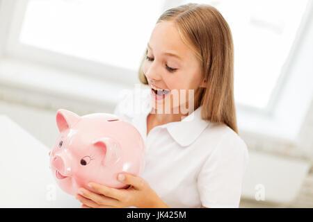 glückliches Mädchen mit Sparschwein zu Hause - Stockfoto
