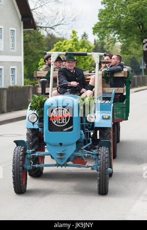 Junge Männer und Frauen im bayerischen Kostüme sitzen auf einem Anhänger, gezogen von einen alten Traktor, Ankunft - Stockfoto