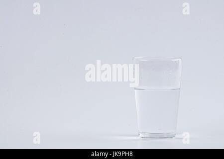 Wasser gießen in klarem Glas auf weißem Hintergrund - Stockfoto