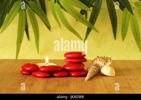Kleinen roten Steinen, die in Spalten im Zen Lebensstil mit einer Kerze und Strand Muscheln auf Bambus-Holz-Boden - Stockfoto