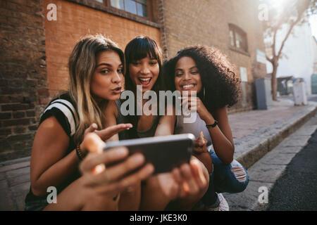 Freundinnen im Freien sitzen und Selfie mit Ihrem Smartphone zu machen. Multi ethnischen Gruppe von Frauen hängen in der Stadt und unter Selbstbildnis mit