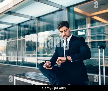 Junger Geschäftsmann warten und überprüfen mit Handy. Geschäftlich unterwegs, auf Bank sitzend und mit Blick auf - Stockfoto