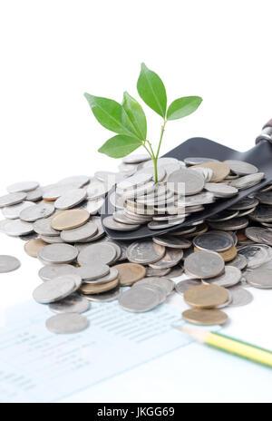Pflanze wächst aus Silbermünzen auf Gartenarbeit Kelle isoliert auf weißem Hintergrund, Ersparnis, Investition und - Stockfoto