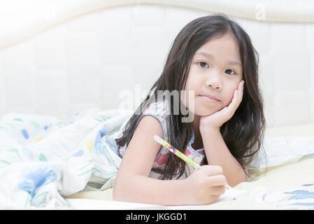 süße asiatische Mädchen schreiben Tagebuch auf dem Bett - Stockfoto