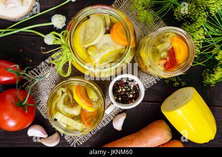 Eingelegtes Gemüse: Gemüse Sortiment (Zucchini, Paprika, Karotten, Tomaten, grüne Erbsen) in Gläsern auf einem dunklen - Stockfoto
