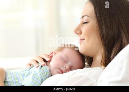 Profil von eine glückliche Mutter mit ihrem Baby auf einem Bett zu Hause schlafen - Stockfoto