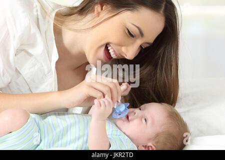 Glückliche Mutter geben einen Schnuller für ihr Baby auf einem Bett - Stockfoto