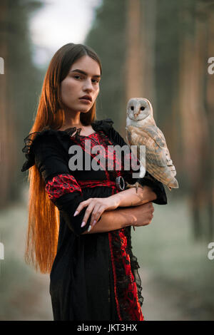 Porträt eines Mädchens mit langen Haaren in roten und schwarzen Kleid im Wald mit Eule. Eule sitzt auf der Hand. - Stockfoto