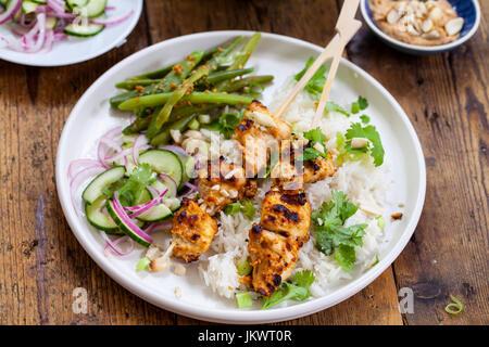 Satay-Hähnchen-Spieße mit grünen Bohnen, Reis und Gurkensalat - Stockfoto