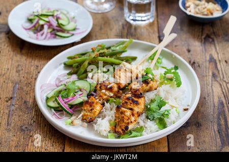 Satay-Hähnchen-Spieße mit grünen Bohnen, Reis und Gurkensalat