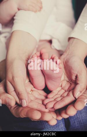 Mama und Papa halten Baby Beine Stockfoto