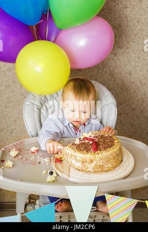 Ein Jahr alter Junge sitzt im Hochstuhl und seinen Kuchen schmecken. Ersten Geburtstag feiern Konzept. Kuchen-smash - Stockfoto