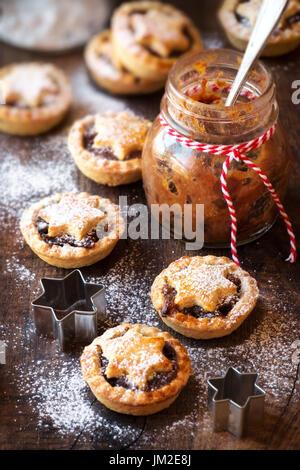 Traditionelle festliche Weihnachten Mince Pies mit ein Glas hausgemachte Hackfleisch und ein leeres tag - Stockfoto