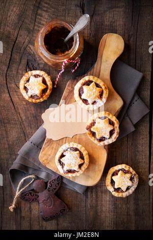 Traditionelle festliche Weihnachten Mince Pies mit ein Glas hausgemachte Hackfleisch und ein leeres Tag. Draufsicht - Stockfoto