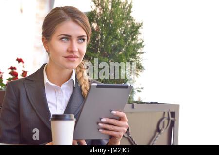 Attraktive junge Frau Kaffee trinken und ihr Touchscreen-Tablet zu lesen, während die Standortwahl im Café. Business - Stockfoto