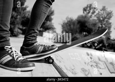 Nahaufnahme eines kaukasischen Jünglings skateboarding in ein Outdoor-Skate-Park, in schwarz und weiß - Stockfoto