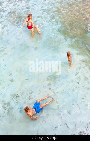 Familie Lifestyle. Vater, Mutter mit Kindern entspannen Sie im natürlichen Meerwasser Pool an Engels Billabong. - Stockfoto