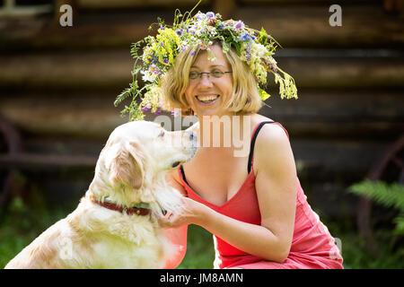 junge Frau mit Kranz auf dem Kopf und einem Hund, golden retriver - Stockfoto