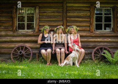 drei junge Erwachsene Frauen mit einem Hund sitzen auf einer Bank von einem Holzhaus - Stockfoto