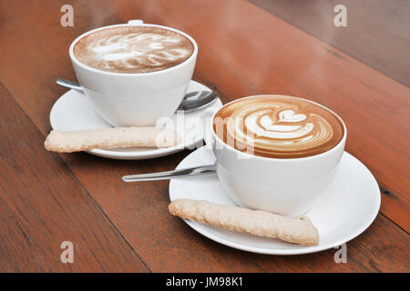 zwei Tassen Latte Art Kaffee in eine weiße Tasse auf hölzernen Hintergrund Stockfoto