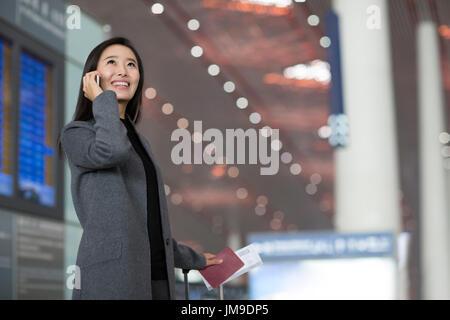 Chinesische Geschäftsfrau, reden über Handy am Flughafen - Stockfoto