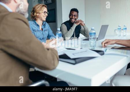 Lächelnd Geschäftsfrau in Treffen mit Kollegen im Konferenzraum. Managerin führt Brainstorming-Sitzung im Konstruktionsbüro. - Stockfoto