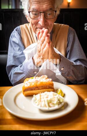 Alter Mann reibt seine Hände im Vorgriff auf seine Lieblings-Essen in einem Restaurant. Lobster roll in Küste von - Stockfoto