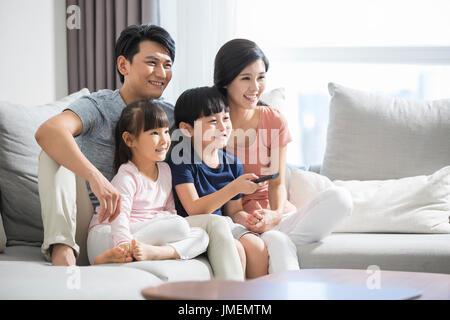 Glückliche junge chinesische Familie vor dem Fernseher - Stockfoto
