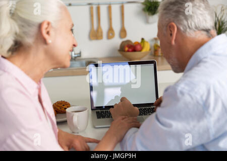 Bild anzeigen Reife liebende Paar Familie sitzen in der Küche mit Laptop-Computer zurück. Auf der Suche zur Seite. - Stockfoto