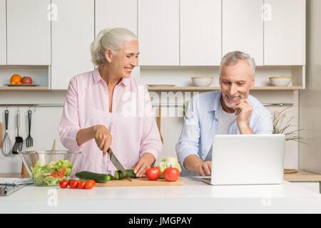 Bild von Reifen liebenden paar Familie stehen in der Küche mit Laptop-Computer und Kochen Salat. Auf der Suche zur - Stockfoto