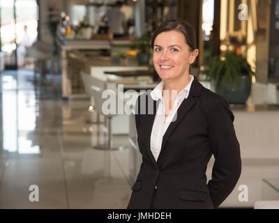 Elegante und fröhliche Frau Angestellte an der Rezeption - Stockfoto