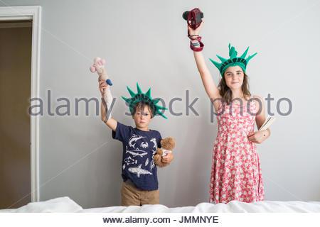 Ein kleiner Junge und ein junges Mädchen darstellen wie die Statue of Liberty gegen eine graue Wand. - Stockfoto