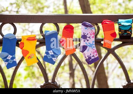 Verschiedene bunte Kinder Socken an eine Wäscheleine im Freien hängen. Viele kleine Socken auf einer Wäscheleine - Stockfoto