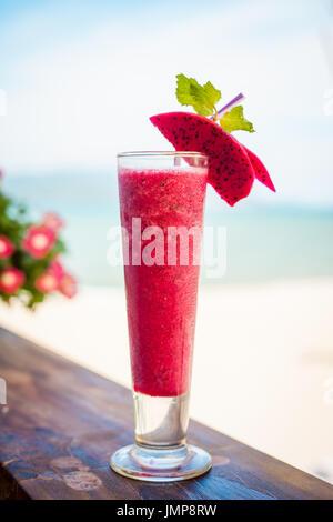 Nahaufnahme von Glas mit erfrischenden orange Cocktail mit Drachenfrucht am Strand. - Stockfoto