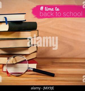 Zurück zu Schule Text mit Hashtag gegen Lupe mit Stapel Bücher auf Tisch - Stockfoto