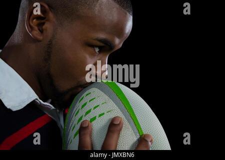 Nahaufnahme eines männlichen Spieler küssen Rugby-Ball auf schwarzem Hintergrund - Stockfoto