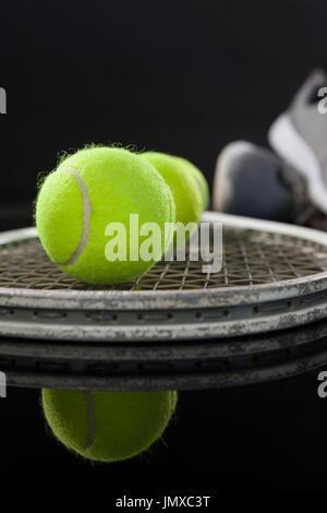 Nahaufnahme von fluoreszierenden gelben Tennisbällen auf Schläger von Sportschuhen mit Reflektion auf schwarzem - Stockfoto