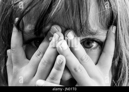 Verbergen und enthüllen: schwarz und weiß in der Nähe Porträt eines jungen Mädchens versteckt sich hinter ihren - Stockfoto