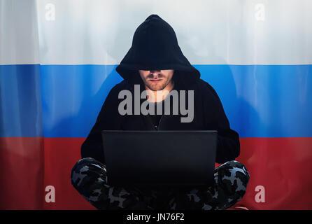 Hacker in einem dunklen Kapuzenpullover sitzen vor einem Notebook auf dem Hintergrund der russischen Flagge. - Stockfoto