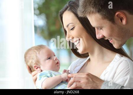 Stolze Eltern halten und spielen mit ihrem Baby zu Hause - Stockfoto