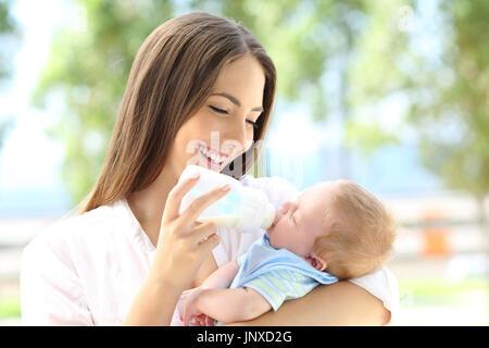 Portrait eines glücklichen Mutter, das Füttern mit der Flasche auf ihr Baby im Freien - Stockfoto