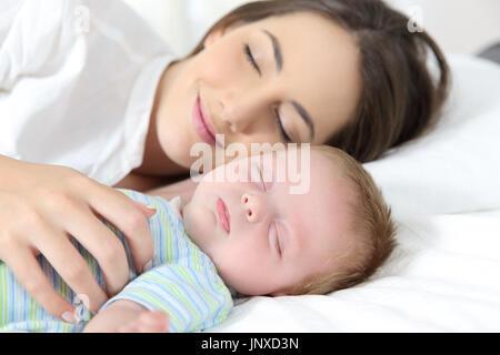 Porträt eines glücklichen Mutter und Baby schlafen zusammen im Bett - Stockfoto