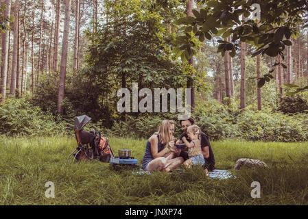 Glückliche Familie mit Abendessen im Wald. Camping Familienkonzept. - Stockfoto