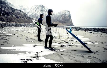 Zwei Surfer mit Neoprenanzügen und Surfbretter stehen an einem Strand mit Bergen im Hintergrund. - Stockfoto