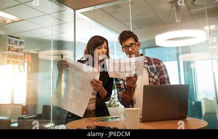 Junge Designer arbeiten zusammen am Schreibtisch. Business-Profis mit Blick auf die Bilder für ihre neue Design - Stockfoto